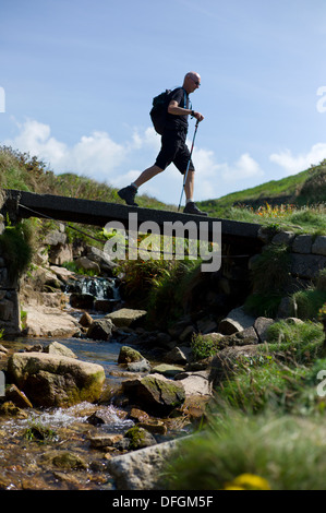 Rambler crosses a wooden bridge in Cot Valley, Porth Nanven near St. Just  Cornwall UK Credit: David Levenson/Alamy - Stock Photo