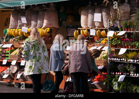 Customers Browsing Outside A greengrocers Fruit and Veg Shop Display UK - Stock Photo