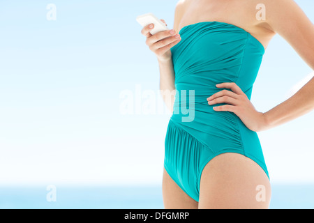 Woman in bathing suit using cell phone - Stock Photo