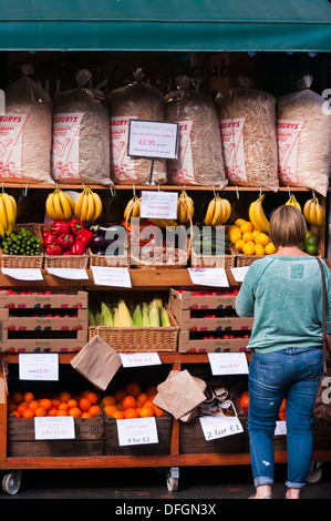 Shopper Browsing Outside A greengrocers Fruit and Veg Shop Display UK - Stock Photo