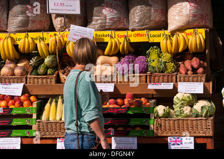 Housewife Browsing Outside A greengrocers Fruit and Veg Shop Display UK - Stock Photo