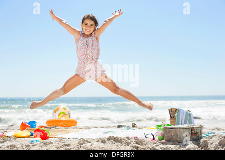 Girl jumping on beach - Stock Photo