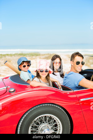 Portrait of smiling family in convertible at beach - Stock Photo