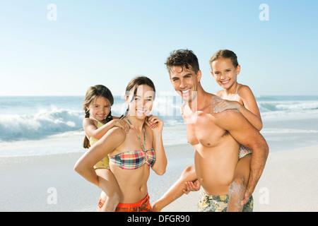 Parents carrying daughters piggyback on beach - Stock Photo