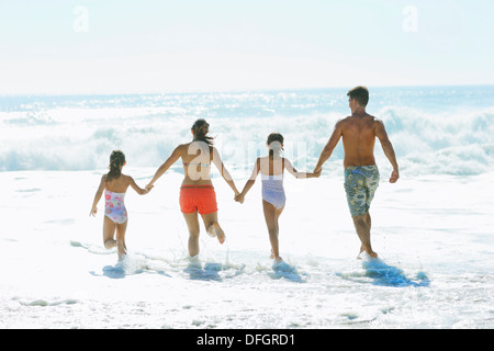 Family running into surf at beach - Stock Photo