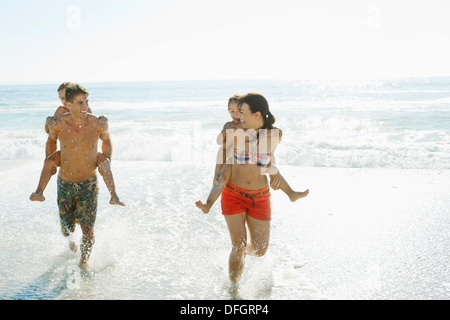 Parents carrying daughters piggyback in surf at beach - Stock Photo