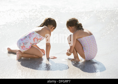Girls playing together in surf on beach - Stock Photo