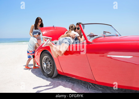 Family packing convertible on beach - Stock Photo