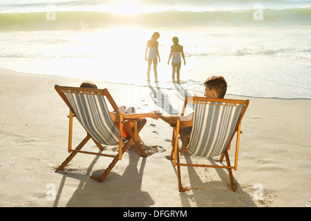 Parents watching daughters play in surf at beach - Stock Photo