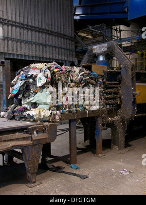 Bale of waste plastic on hydraulic press in recycling plant. The plastic is separated from household waste - Stock Photo