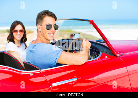 Couple driving convertible on beach - Stock Photo