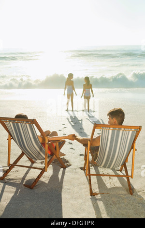 Parents watching daughters on beach at sunset - Stock Photo