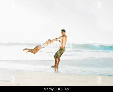 Father swinging daughter on beach - Stock Photo