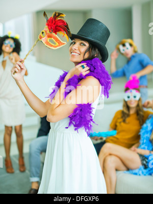 Woman wearing decorative hat with mask at party - Stock Photo