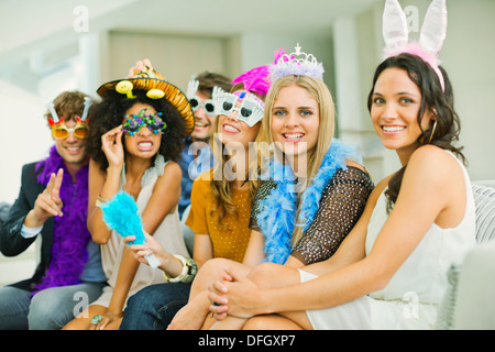 Friends wearing decorative glasses and headpieces at party - Stock Photo
