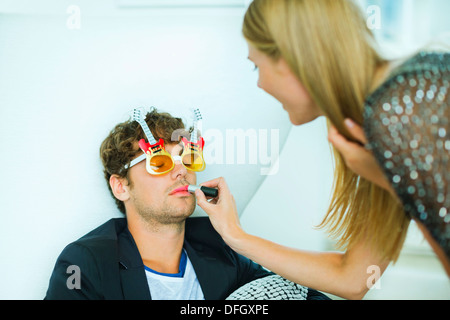 Woman applying lipstick to sleeping man at party - Stock Photo