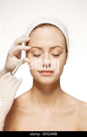 Doctor injecting botox into woman's face - Stock Photo