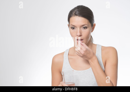 brunette woman taking medication with a glass of water - Stock Photo