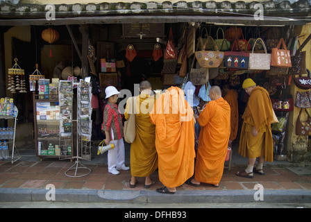 Group of male buddist monks, accompained by a tourist guide, shopping souvenirs in Hoi An, the best preserved town - Stock Photo