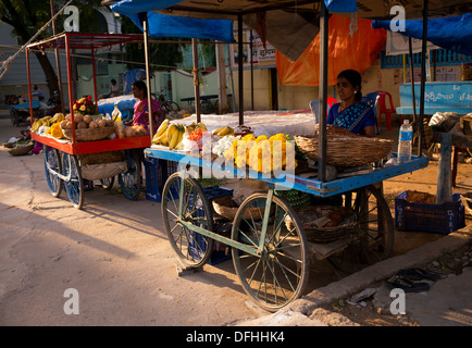 Indian women selling fruit and flowers from a cart in an Indian street. Puttaparthi, Andhra Pradesh, India - Stock Photo