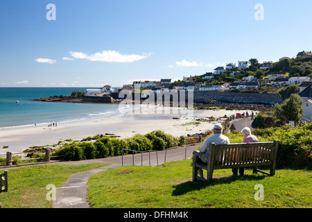 Couple sitting on bench overlooking the sea front, Coverack, Cornwall Stock Photo