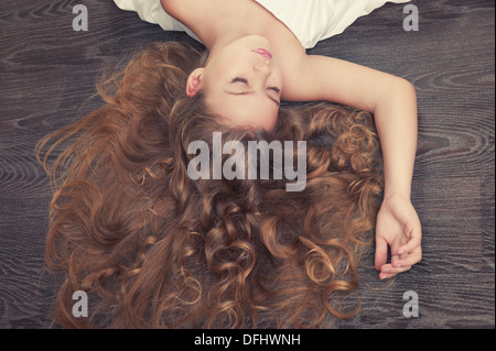 Portrait of beautiful sleeping girl with curly hair - Stock Photo