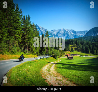 Bikers on mountainous road, touring across Alpine mountains, along little village, beautiful landscape, travel and - Stock Photo