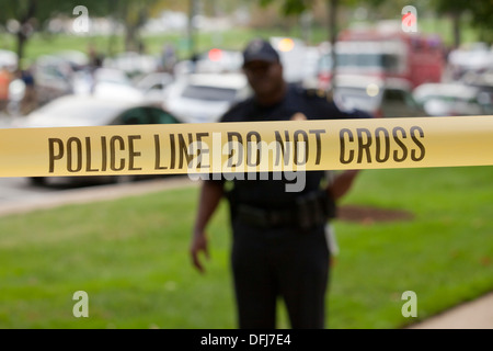 Policeman standing behind police line tape at a crime scene - Washington, DC USA - Stock Photo