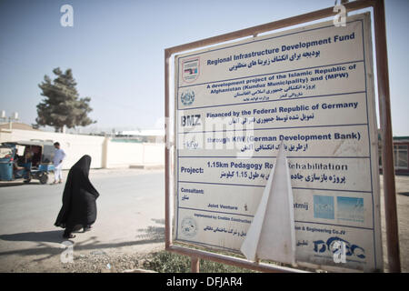 Kunduz, Afghanistan. 05th Oct, 2013. A woman walks past a weathered sign, which refers to the financing of a road - Stock Photo