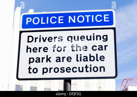 Sign warning drivers of prosecution if they queue on the road while waiting to enter the car park - Stock Photo