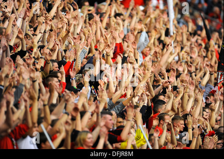 supporters of german football Bundesliga club Bayer 04 Leverkusen raise their hands in support - Stock Photo