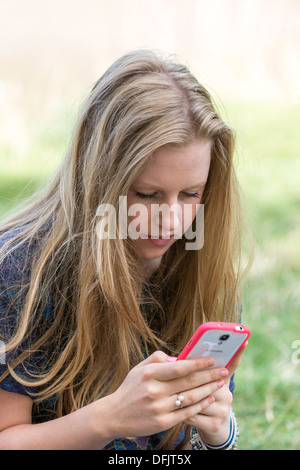 YOUNG GIRL, TEENAGER AGED SEVENTEEN,TEXTING ON CELL /MOBILE PHONE OUTDOORS - Stock Photo
