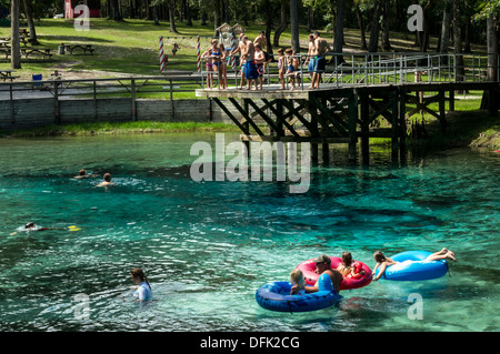 Man tows young girls across spring in inflatable pool tube floats with men, women and children standing on a dive - Stock Photo