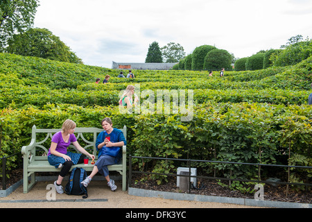 LONDON, UK - AUGUST 13: Side view of people walking up shrubbery maze leading to the grounds of Kensington Palace, - Stock Photo