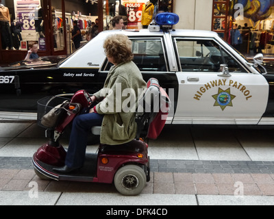 A senior lady in a mobility mobile rides past a California Highway Patrol police car - Stock Photo