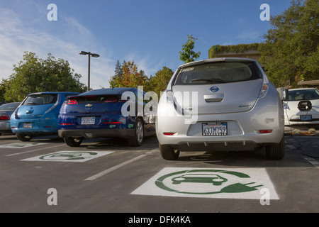 EV symbol painted on parking spaces for to plug-in electric cars in a company parking lot - Stock Photo