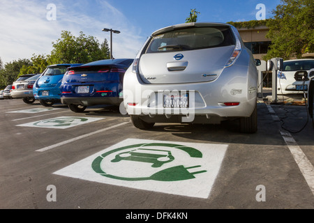 EV symbol painted on parking spaces reserved for plug-in electric cars in a company parking lot - Stock Photo