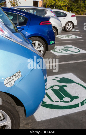 EV symbol painted on parking spaces at a company parking lot indicating spots are reserved for plug-in electric - Stock Photo
