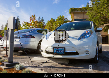 Nissan Leaf plug-in electric car parked in an EV parking spot at work and plugged into a charging station - Stock Photo