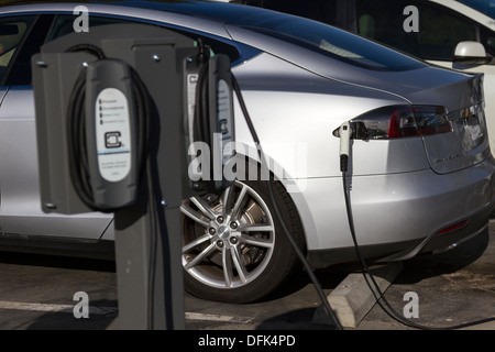 Tesla Model S plug-in electric car plugged into a charging station in a company parking lot. Focus is on the connector - Stock Photo