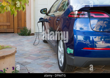Plug-in electric car with carpool sticker parked in driveway, with connector plugged in and charging at home - Stock Photo