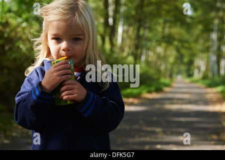 Close up of child blond girl drinking juice from box outside on walk pathway - Stock Photo