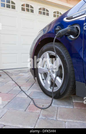 Chevrolet Volt plug-in hybrid electric car with connector plugged in and charging, parked at home in a driveway - Stock Photo