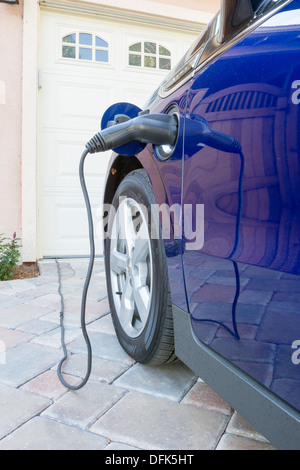 Plug-in hybrid electric car with connector plugged and charging parked at home in a driveway - Stock Photo