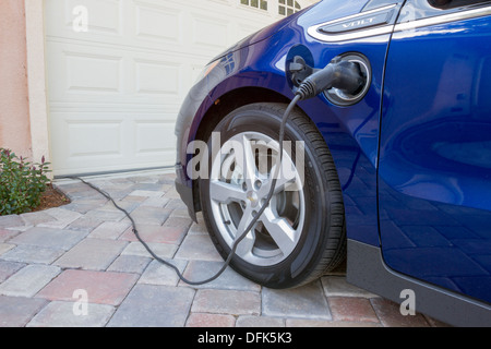 Chevrolet Volt plug-in electric car with connector plugged in charging, at home in a driveway - Stock Photo