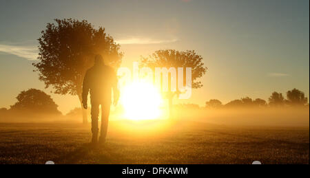 Peterborough, Cambridgeshire, UK. 6th October 2013.  A person out for a walk through the early morning mist at Nene - Stock Photo