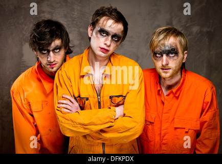 Three guys in orange uniforms indoors - Stock Photo