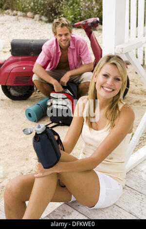 Happy couple having a break on a country trip with a scooter - Stock Photo