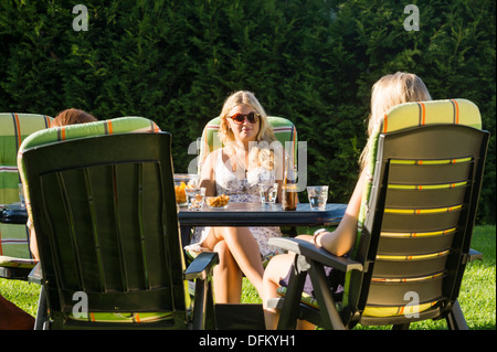 Beautiful woman enjoying garden party with female friends - Stock Photo