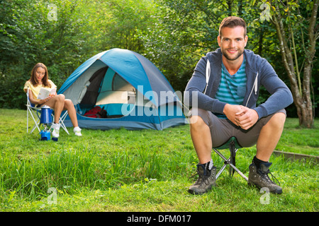 A young couple relaxing in front of a tent - Stock Photo